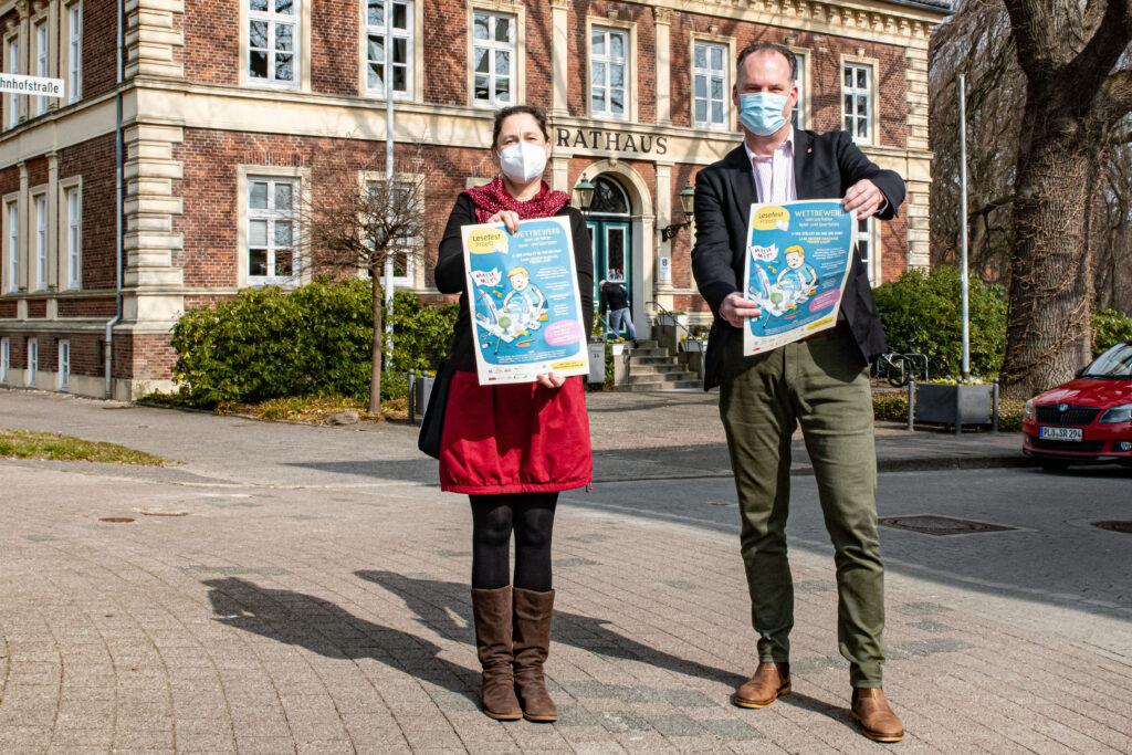 Illustratorin Franziska Ludwig und Bürgermeister Björn Demmin präsentieren das Plakat des Lesefest-Wettbewerbs